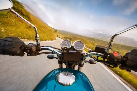 Motorcycle driver riding in Alpine highway, handlebars view, Dolomites, Europe. 免版税图像