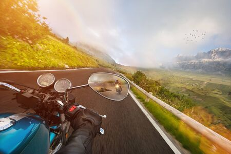 Motorcycle driver riding in Alpine highway, handlebars view, Dolomites, Europe. Stock Photo