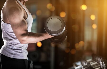 Muscular young man doing weight exercise for biceps with dumbbells Stock Photo