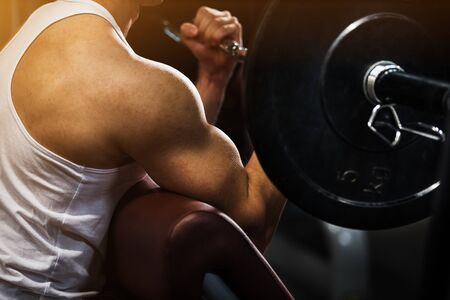 Giovane muscolare che fa esercizio con i pesi per bicipiti con manubri Archivio Fotografico