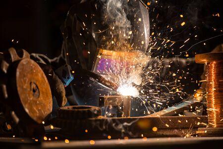 Welder is welding metal part in factory Stockfoto