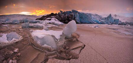 Famous Fjallsarlon glacier and lagoon with icebergs swimming on frozen water, sunset. Standard-Bild - 130954534