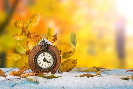 Autumn time change concept. maple leaves and vintage clock