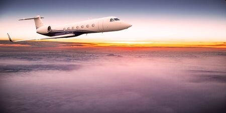 Private jet plane flying above dramatic clouds during sunset. Foto de archivo