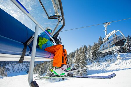 Skier sitting at ski lift in high mountains during sunny day. Фото со стока