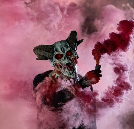 Guy in devil mask standing with smoke bombs, portrait