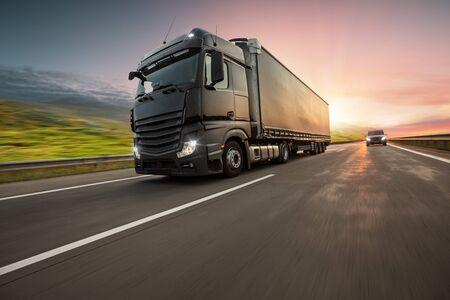 Vrachtwagen met container op snelweg, vrachtvervoer concept. Scheereffect. Stockfoto