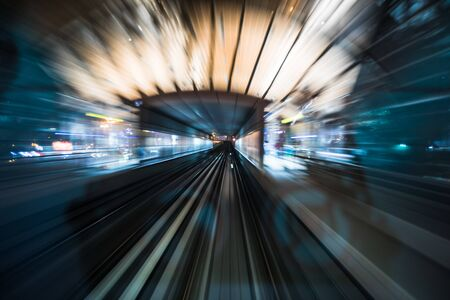Tran running on rails in a night city., blurred motion with light. Фото со стока