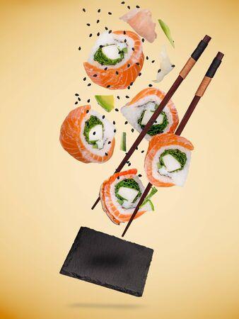 Trozos de delicioso sushi japonés congelados en el aire sobre fondo de color pastel. Foto de archivo