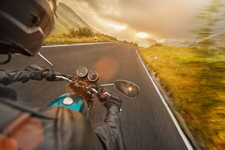 Motorcycle driver riding in Alpine highway, handlebars view, Dolomites, central Europe.