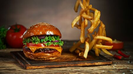 French fries fall next to cheeseburger, lying on vintage wooden cutting board, Freeze motion. 版權商用圖片
