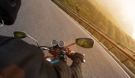 Motorcycle driver riding in Alpine highway, handlebars view, Dolomites, Europe.