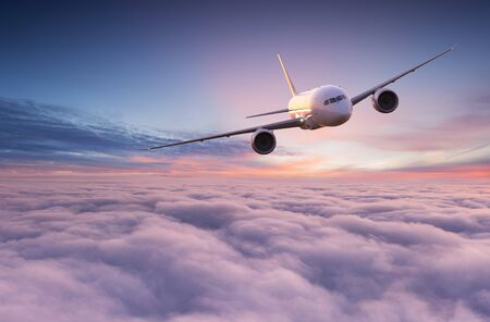 Avion de ligne commercial volant au-dessus de nuages spectaculaires. Banque d'images