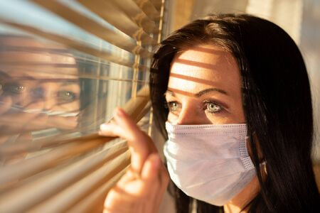 Woman with veil looking out of home window, concept of quarantine during viral pandemic.