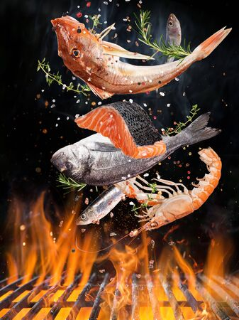 Tasty fishes flying above cast iron grate with fire flames. Stock Photo
