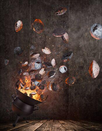 Kettle grill with hot briquettes and cost iron grate flying in the air. Freeze motion barbecue concept. Standard-Bild - 145913698