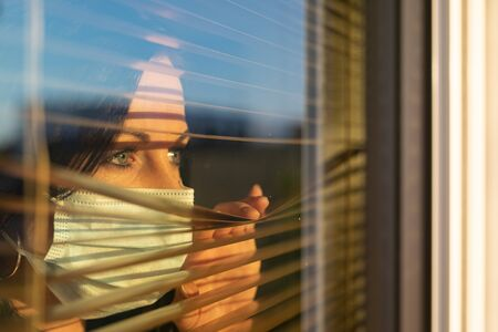 Woman with veil looking out of home window, concept of quarantine during viral pandemic. Standard-Bild - 146125246