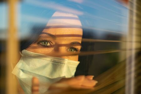 Woman with veil looking out of home window, concept of quarantine during viral pandemic. Standard-Bild - 146125351