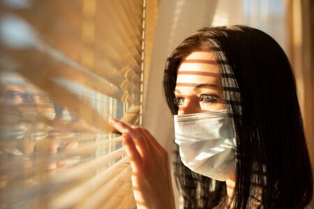 Woman with veil looking out of home window, concept of quarantine during viral pandemic. Standard-Bild - 146125352