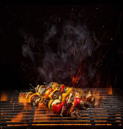 Tasty skewers on the grill with fire flames Standard-Bild - 145914352