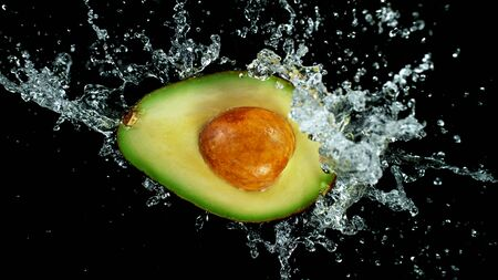 Freeze motion of sliced avocado with splashing water isolated on white background Standard-Bild - 145914025