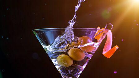 Freeze motion shot of olives splashing into martini. Standard-Bild - 145914117