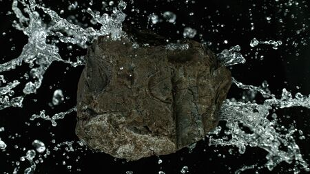 Piece of coal wit water splashing. Cosmetic concept of skin and face care. Standard-Bild - 146135360