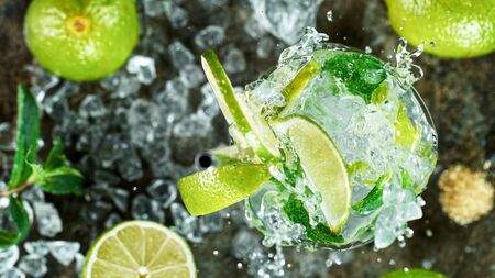 Top view shot of fresh mojito cocktail with fresh lime and mint leaf on black stone background, Freeze motion Standard-Bild - 145914321