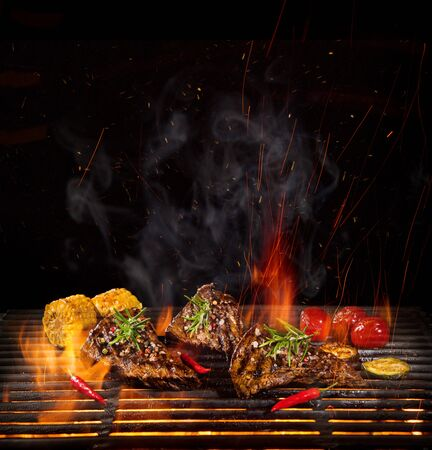 Tasty beef steaks on the grill with fire flames Standard-Bild - 145914336