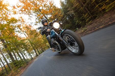 Motorcycle driver riding in autumn forest Stok Fotoğraf