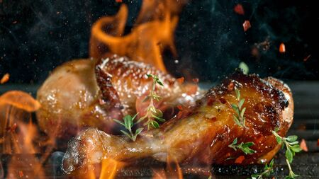 Tasty chicken legs on cast iron grate with fire flames.