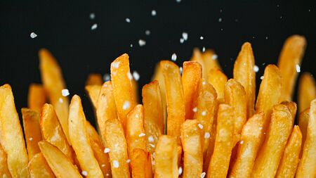 Freeze Motion Detail Shot of adding Salt on French Fries