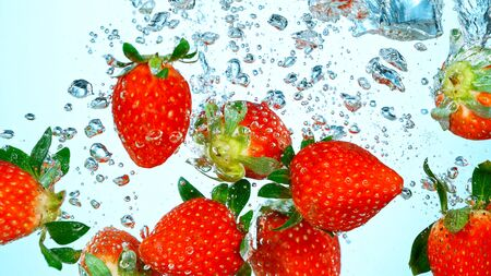 Freeze Motion Shot of Fresh Strawberries falling into water