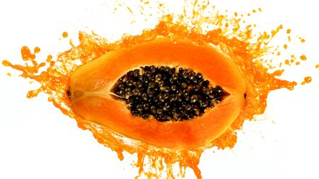 Freeze motion of sliced papaya with splashing juice. Imagens