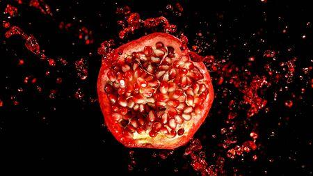 Freeze motion of sliced pomegranate with splashing juice. Standard-Bild