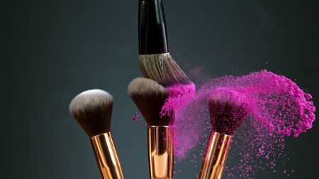 Makeup brushes touch each other on dark background