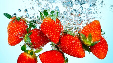 Freeze Motion Shot of Fresh Strawberries falling into water
