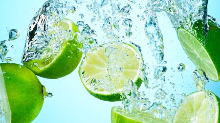 Freeze Motion Shot of Fresh Limes falling into water Standard-Bild