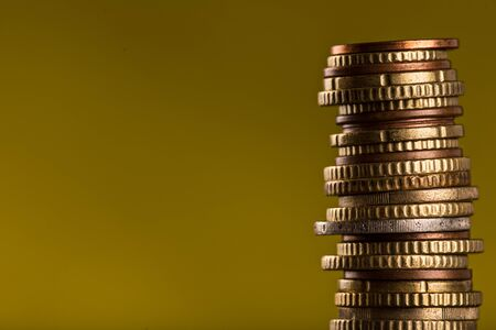 Coins stacked isolated on dark yelow background Standard-Bild