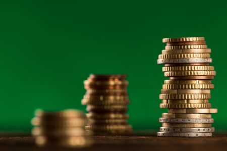 Coins stacked isolated on dark green background