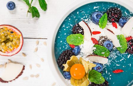Smoothie bowl with fresh berries, nuts, seeds, fruit and vegetables.