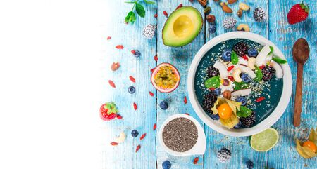 Smoothie bowl with fresh berries, nuts, seeds, fruit and vegetables. Zdjęcie Seryjne - 149604177