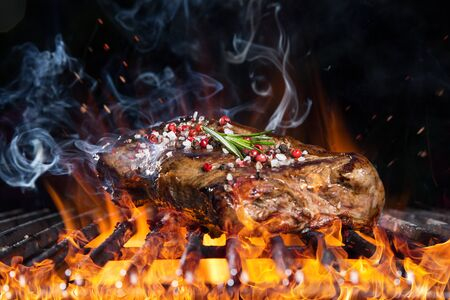 Tasty beef steak on cast iron grate with fire flames.