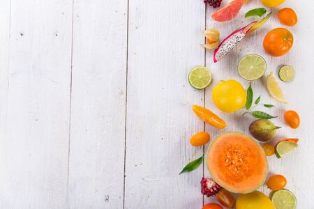 Citrus fruits on white wooden table.