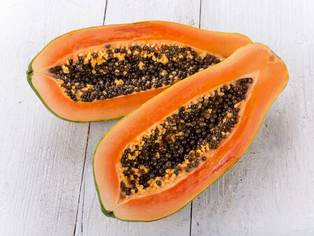 Fresh papaya cut in half on vintage blue wooden table. Zdjęcie Seryjne - 149854080