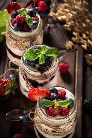 Tasty yoghurts with muesli, fresh berries and jam.