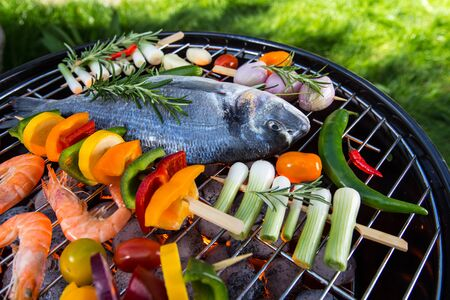 Grilled sea fishes with vegetable, skewers and prawns on a barbecue grill.