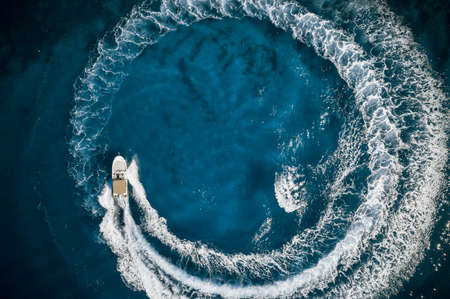 Speed boat in mediterranean sea making a cyrcle from bubbles, aerial view