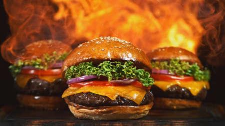 Tasty cheeseburgers, lying on vintage wooden cutting board.