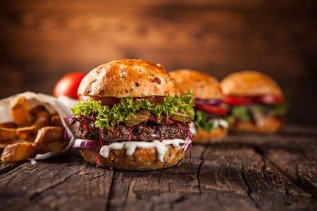 Tasty burgers on wooden table. Stockfoto